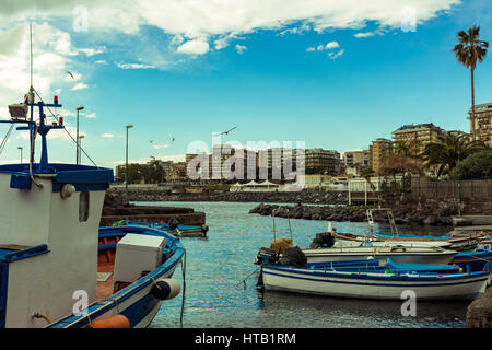 Several small colorful boats are anchored in the harbor of Catania, SIcily-Italy on the coast of the Mediterranean - Stock Photo