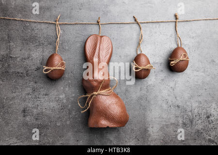Delicious traditional Easter chocolate bunny and eggs hanging on a string - Stock Photo