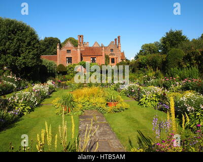 Chenies Manor overlooking the colourful sunken garden in July, in full sun with bright blue sky, pink dahlias, hosta, - Stock Photo