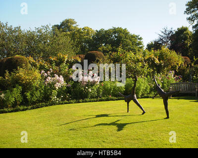 Statues on the lawn at Chenies Manor garden, Buckinghamshire with bench seat, pink herbaceous plants with shrubs, - Stock Photo