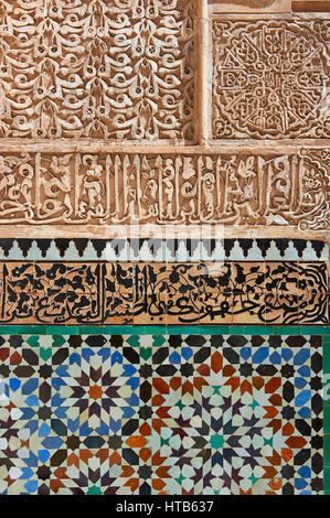 Berber arabesque Morcabe plasterwork and Zellige tiles of the 14th century Ben Youssef Madersa (Islamic college) - Stock Photo