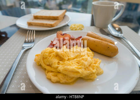 Breakfast with scambled eggs, sausage and bacon - Stock Photo