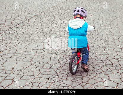 Kid riding on a bike from behind - Stock Photo