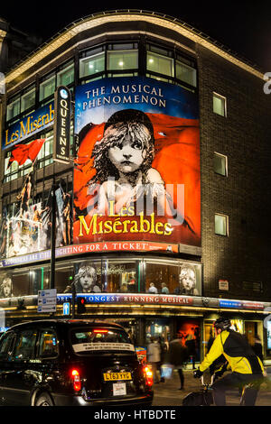 London's West End at night with Les Miserables at Queens Theatre in Shaftesbury Avenue. - Stock Photo