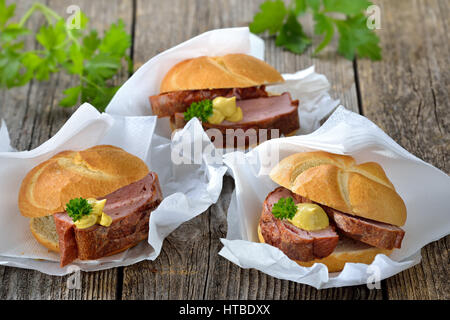 Bavarian takeaway food: Three rolls with baked meat loaf and mustard on wrapping paper with a napkin