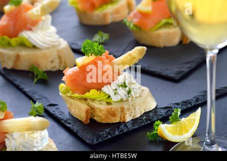 Delicious canapes with German white asparagus, cream cheese with herbs, smoked salmon on Italian bread with lettuce - Stock Photo