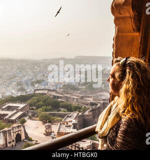 A woman looks out over the city of Jodhpur from a window high in Mehrangarh Fort. Rajasthan, India. - Stock Photo
