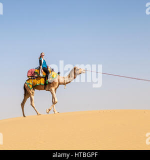 A woman riding a camel on a sand dune in the Thar desert, Rajasthan, India. - Stock Photo