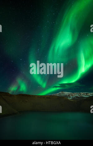 Green Northern lights or Aurora Borealis above Viti Crater, Iceland - Stock Photo