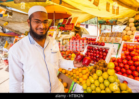 An Indian man in a fruit market in Pune, India holding up apples from Washington State, USA. - Stock Photo