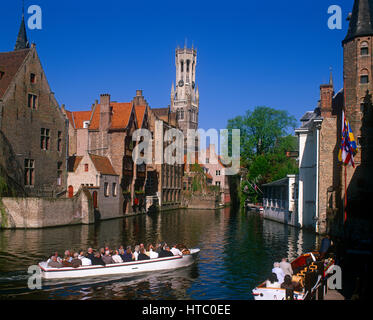 Pleasure boats and tourists on the Djiver Canal with the Belfry in background, Bruges, Belgium. - Stock Photo