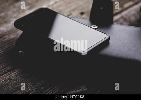 Black smartphone on wooden background. - Stock Photo