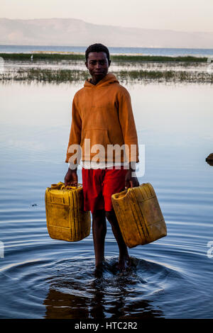 A Teenage Boy Collects Water From The Lake In Containers, Lake Awassa, Ethiopia - Stock Photo