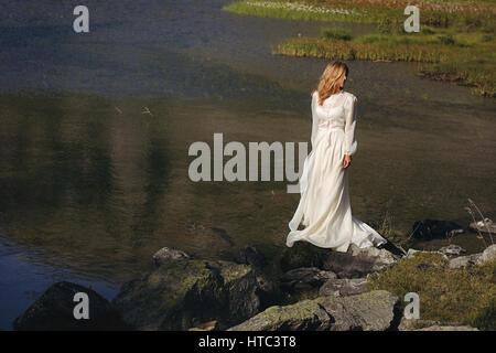 Sad bride posing in a mountain lake. Romantic and dreamy - Stock Photo
