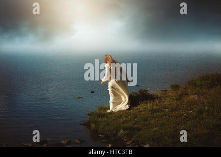 Woman looking at surreal waters. Photomanipulation with dreamy colors - Stock Photo