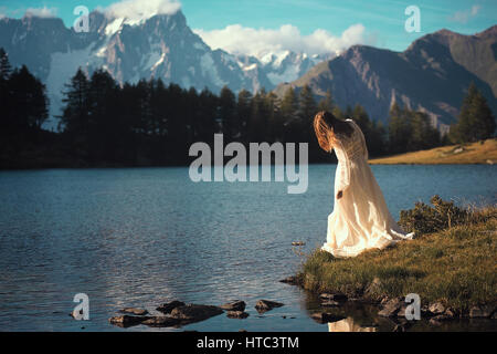 Woman posing in mountain lake at sunset. Romantic and dreamy