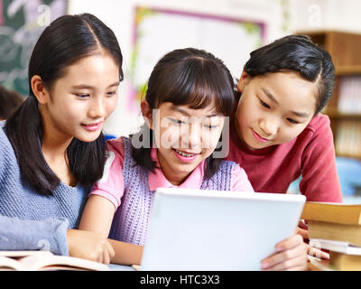 three asian elementary school girls friends looking at a tablet together during break in classroom. - Stock Photo