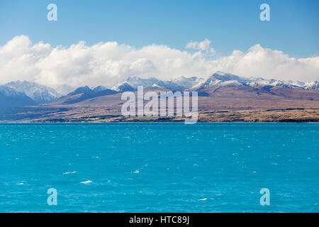 Twizel, Canterbury, New Zealand. View across the turquoise waters of Lake Pukaki to the snow-capped peaks of the Southern Alps.