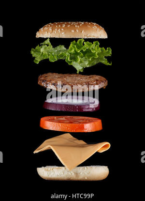 Stacked juicy hamburger ingredients isolated on black. Fast food menu cover - Stock Photo