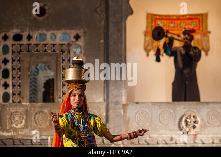 A trumpeter heralds a dancer carrying a fire pot on her head at Bagore Ki Haveli evening show in Udaipur - Stock Photo