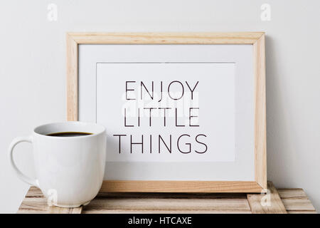 a wooden-framed picture with the text enjoy little things written in it and a cup of coffee, on a rustic wooden - Stock Photo