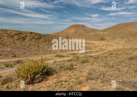 Image of a car on a dirt road in the landscape of Guelmim-Es Semara in Morocco right next to the Atlantic coast. - Stock Photo