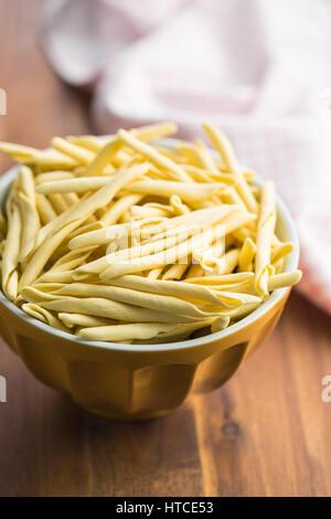 Raw italian pasta in bowl. - Stock Photo