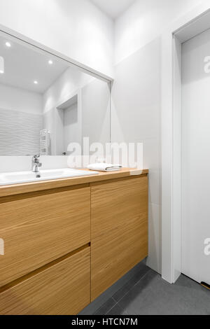 Wide mirror over wood cabinets in clean, white bathroom - Stock Photo