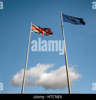 EU flag above UK flags above a single white cloud - Stock Photo