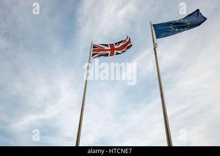 Looking up at EU and UK flags blowing in the wind - Stock Photo