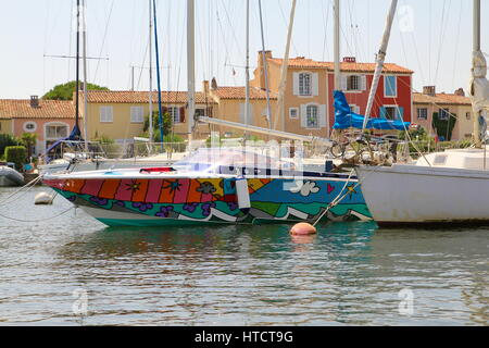 PORT GRIMAUD, FRANCE, AUGUST 28 2015: Rainbow colored boat in the port, with traditional Provencal houses - Stock Photo