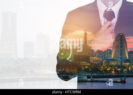 Double exposure of Businessman in suit tying the necktie against the city - Stock Photo