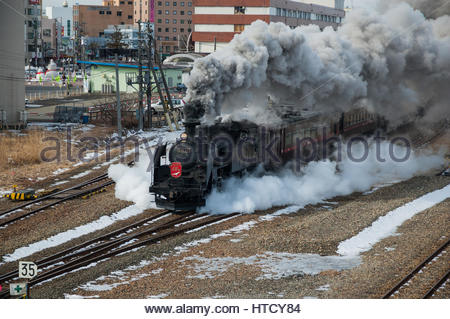 Japanese steam special in Hokkaido winter with a Class C11 tank locomotive leaves Kushiro station in cloud of smoke. - Stock Photo