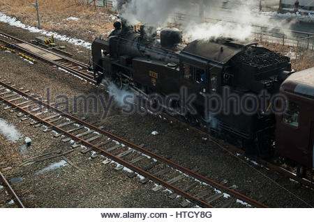 Japanese steam special in Hokkaido winter with a Class C11 tank locomotive leaves Kushiro station - Stock Photo