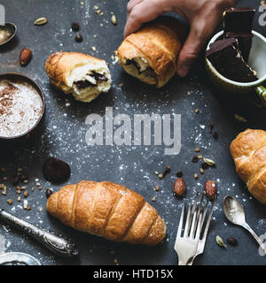 Croissants with chocolate. Eating fresh croissants. Hand picking croissant. Square crop, closeup view. - Stock Photo