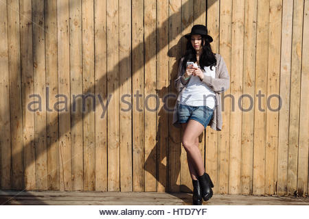 Elegant beautiful hipster woman texting on smartphone in the city - Stock Photo