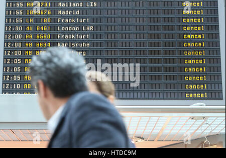 Berlin, Germany. 10th Mar, 2017. Two passengers walk past an electronic screen showing cancelled flights at Tegel - Stock Photo