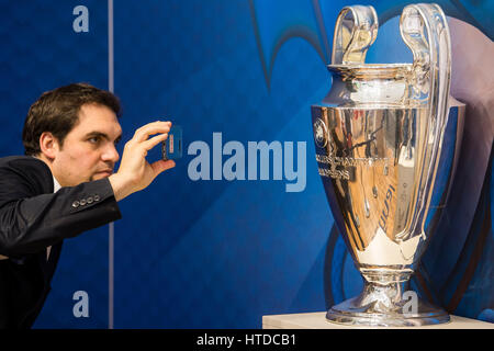 Berlin, Germany. 10th Mar, 2017. A visitor takes a photo with the cup of the UEFA Champions League at the stand - Stock Photo
