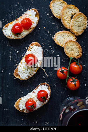 Toast with white cheese spread and roasted cherry tomatoes and glass of red wine over black background. Top view - Stock Photo