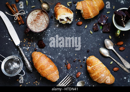 Coffee, croissants, chocolate, spices, nuts and vintage cutlery. Flat lay composition of sweet breakfast food on - Stock Photo