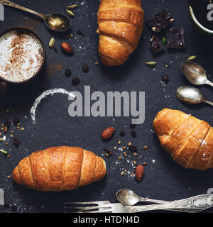 Fresh croissants, coffee, chocolate, nuts and spices over dark background. Top view with copy space. Square crop - Stock Photo