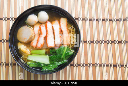 Egg noodle soup with red roast pork on wooden background. - Stock Photo