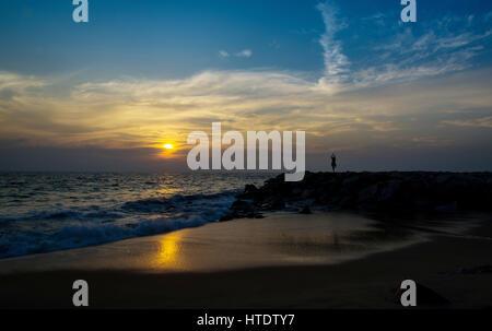 Lady doing suryanamaskar asana on beach during sunset - Stock Photo