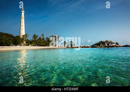 White lighthouse standing on an island in Belitung at daytime surrounded by clear blue green colored ocean water - Stock Photo