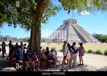 El Castillo, Chichen Itza with tourists sheltering from sun under trees mexico - Stock Photo
