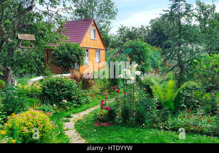 Summer wooden house on background of green garden,  landscape. - Stock Photo