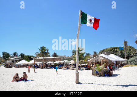 tourists on tulum beach mexico with mexican flag flying - Stock Photo
