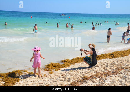 japanese tourist in sunhat takes photo of daughter in pink dress and hat on tulum beach - Stock Photo