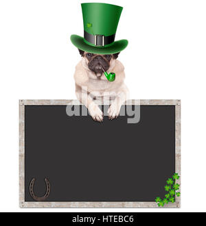 lovely cute pug puppy dog with leprechaun hat for st. patrick's day smoking pipe, leaning on blank chalkboard sign - Stock Photo