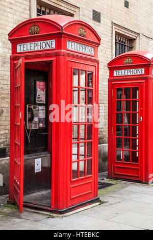 Two red telephone boxes in London, one with open door. - Stock Photo